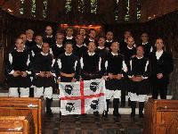 Foto di gruppo del Coro Monte Gonare con la bandiera 4 mori